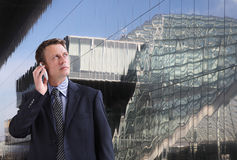 Business man talking on the phone looking up through the glass buildings stock photography