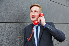Business man talking on red phone Stock Photography
