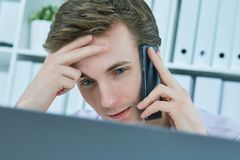 Close-up portrait of white collar talking to customer on mobile phone in office at workplace by laptop. Stock Images