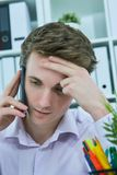 White collar talking to customer on mobile phone in office at workplace by laptop. Stock Photos