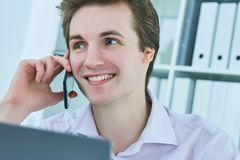 Young white collar talking to customer on mobile phone in office at workplace by laptop. Royalty Free Stock Photo