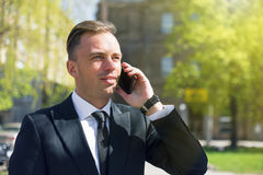 Business man talking on smartphone outdoors Stock Image
