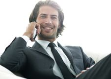 Business man talking on a smartphone while sitting in a comfortable chair. Successful business man talking on a smartphone while sitting in a comfortable chair Stock Image