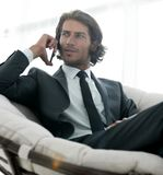 Business man talking on a smartphone while sitting in a comfortable chair. Successful business man talking on a smartphone while sitting in a comfortable chair Stock Photo