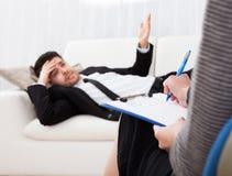 Business man talking to his psychiatrist explaining something Royalty Free Stock Photo