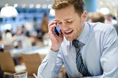 Business man talks on mobile in cafe Stock Photo