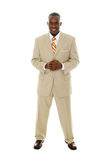 Business Man in Tan Suit. Handsome happy smiling man in tan business suit standing with hands clasped together