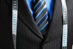 Business man with tape measure. This is an image of business man wearing a tape measure across his suit Royalty Free Stock Photography