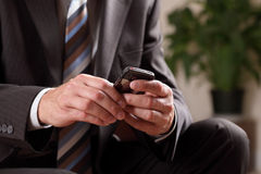 Business man text messaging. Text messaging or checking email on mobile phone whilst waiting for a business meeting Royalty Free Stock Images