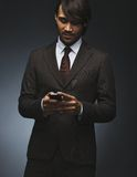 Business man text messaging on his smartphone Royalty Free Stock Image