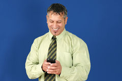 Business man texting on cell phone. Happy and smiling middle aged man or businessman, with salt and pepper hair, reading or texting message on his smart cell Royalty Free Stock Photography