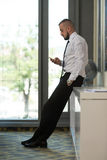 Business Man Texting On Cellphone In Modern Office. Business Man Reading Text Message On A Mobile In A Modern Office Stock Image