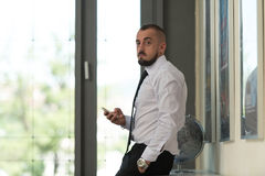 Business Man Texting On Cellphone In Modern Office. Business Man Reading Text Message On A Mobile In A Modern Office Stock Images