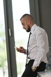 Business Man Texting On Cellphone In Modern Office Royalty Free Stock Images