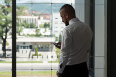 Business Man Texting On Cellphone In Modern Office Stock Images