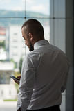 Business Man Texting On Cellphone In Modern Office. Business Man Reading Text Message On A Mobile In A Modern Office Royalty Free Stock Photos