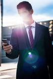 Business man texting on evening outdoors Royalty Free Stock Photos