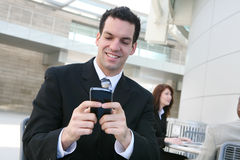 Business Man Texting at Office. A handsome young business man texting on his phone at office building Royalty Free Stock Photography