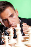 Business man thinking at a chess strategy. Young business man thinking at a chess strategy and looking at his king Stock Photography