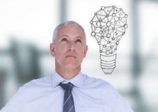 Business man thinking with lightbulb doodle against blurry grey office Royalty Free Stock Images
