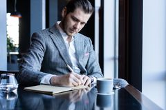 Business man thinks looks out the window, cafe, documents, cup of coffee stock image