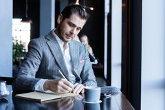 Business man thinks looks out the window, cafe, documents, cup of coffee stock photography