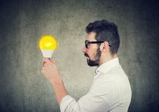 Business man with thoughtful expression looking at bright light bulb. Young business man with thoughtful expression looking at bright light bulb royalty free stock photos