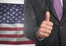 Business man with thumb up against american flag. Digital composite of Business man with thumb up against american flag Royalty Free Stock Photo