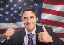 Business man with thumb up against american flag. Digital composite of Business man with thumb up against american flag Stock Image