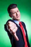 Business man with thumbs down. Hand gesture over green background stock photography
