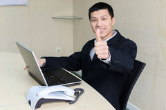 Business man thumbs up. Young confident asia business man thumbs up sit on the chair royalty free stock photography