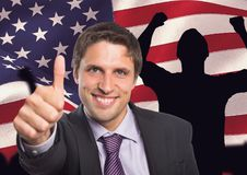 Business man with thumbs up against american flag. Digital composite of Business man with thumbs up against american flag royalty free stock photography
