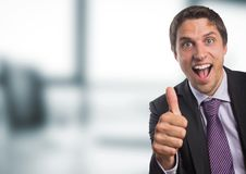 Business man thumbs up against blurry office Royalty Free Stock Photography