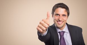 Business man thumbs up against cream background. Digital composite of Business man thumbs up against cream background royalty free stock images