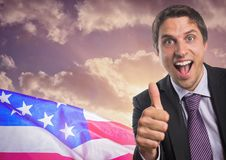 Business man with thumbs up against sunset and american flag. Digital composite of Business man with thumbs up against sunset and american flag royalty free stock photos