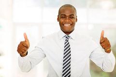 Business man thumbs up. Good looking african business man with thumbs up in modern office royalty free stock image