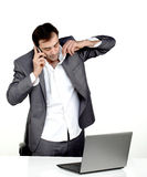 Business man tired and talking. Business man tired talking on a mobile phone in his office with a lap top in front of him Royalty Free Stock Photos