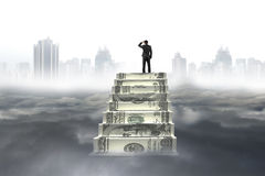 Business man on top of money stairs looking cityscape cloudscape Stock Image