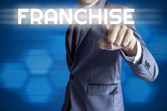 Business man touch modern interface for Franchise. Concept on blue background royalty free stock photography