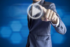 Business man touch play icon on blue background. Stock Images