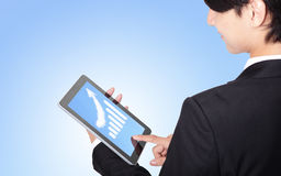 Business man touch tablet pc with growth graph. Business man touch tablet pc, with a growth graph ( made by cloud ) in the air with blue sky, finance and Royalty Free Stock Photography