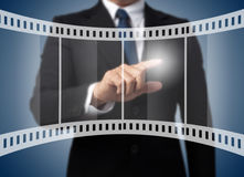 Business man touching on film strip Stock Image