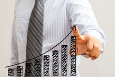 Business man touching a growing graph. Business man touching growing graph on screen Stock Image