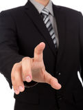 Business man touching an imaginary screen against Stock Photography