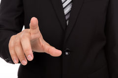 Business man touching an imaginary screen against Royalty Free Stock Photos