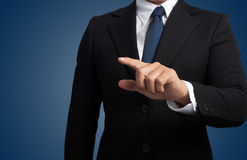 Business man touching an imaginary screen. In blue background Stock Photos