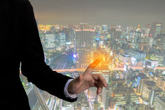 Business man touching an imaginary screen with cityscape. Royalty Free Stock Image