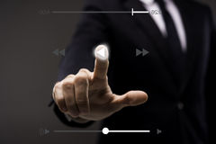 Business man touching imaginery screen with music player Stock Image
