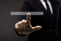 Business man touching imaginery screen with search Royalty Free Stock Image