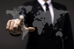 Business man touching imaginery screen with world map. Business man in black suit touching imaginery screen with world map Stock Photo